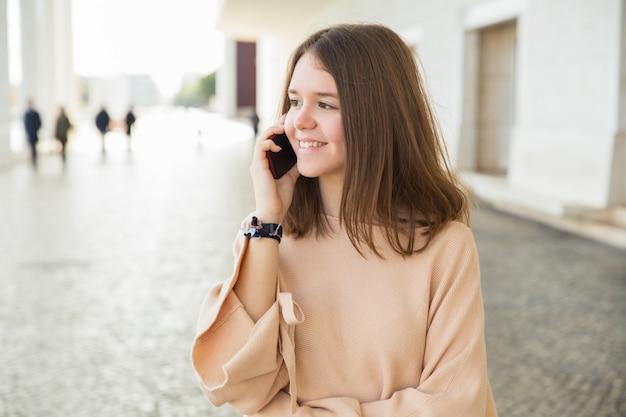 Uśmiechnięty żeński nastolatek opowiada na telefonie komórkowym outdoors