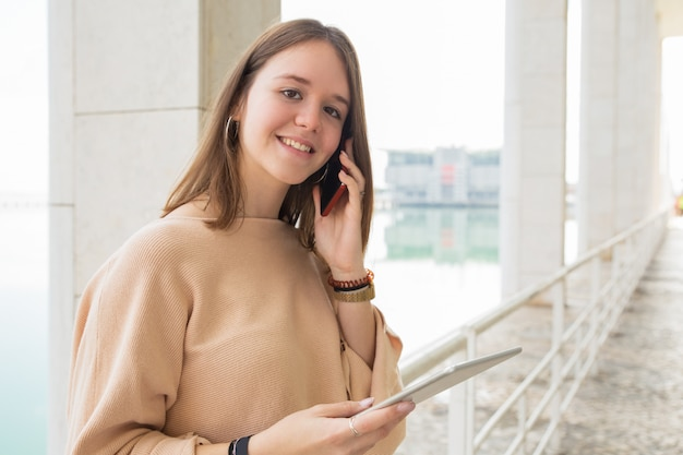 Uśmiechnięty żeński nastolatek używa telefon i pastylkę outdoors