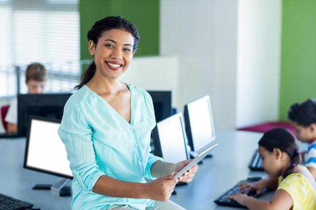 Uśmiechnięty żeński nauczyciel używa laptop