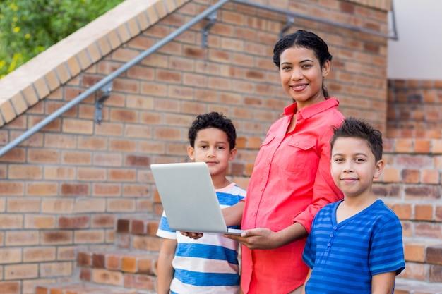 Uśmiechnięty żeński nauczyciel z uczniami używa laptop