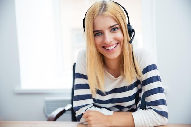 Uśmiechnięty żeński operator z zestawem słuchawkowym