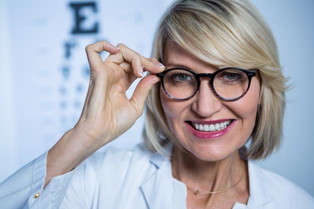 Uśmiechnięty żeński optometrist jest ubranym okulary przeciwsłonecznych