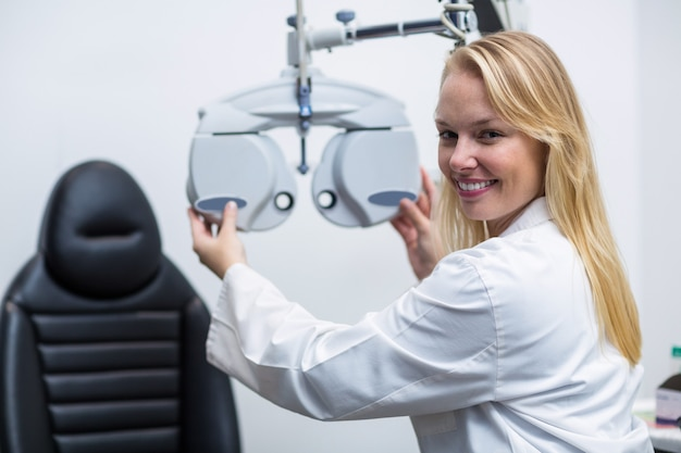 Uśmiechnięty żeński optometrist przystosowywa phoropter