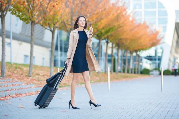 Uśmiechnięty żeński pasażer przystępuje do wyjścia bramy ciągnąc walizkę przez hali lotniska