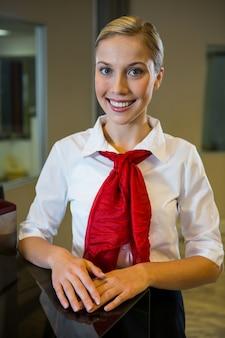 Uśmiechnięty żeński personel stojący przy odprawie na biurku