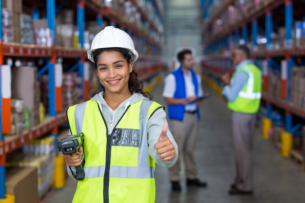 Uśmiechnięty żeński pracownik z kciukiem up
