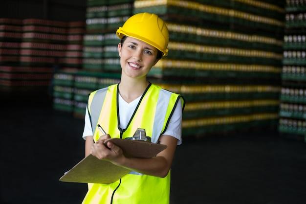Uśmiechnięty żeński pracownika fabrycznego writing na schowku w fabryce