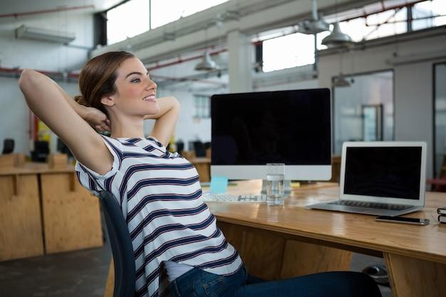Uśmiechnięty żeński projektant graficzny relaksujący na krześle