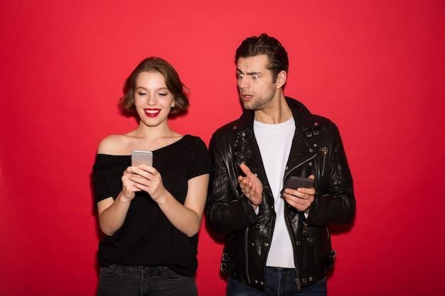 Uśmiechnięty żeński punk używa smartphone podczas gdy mężczyzna podgląda przy on