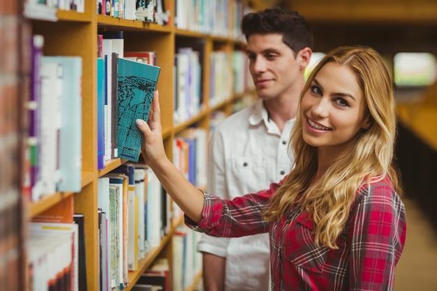 Uśmiechnięty żeński uczeń bierze książkę w bibliotece
