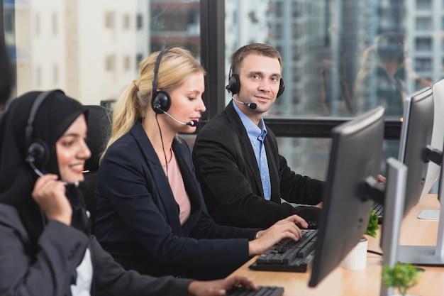 Uśmiechnięty zespół biznesowy operatora obsługi klienta w zestawach słuchawkowych pracy w biurze