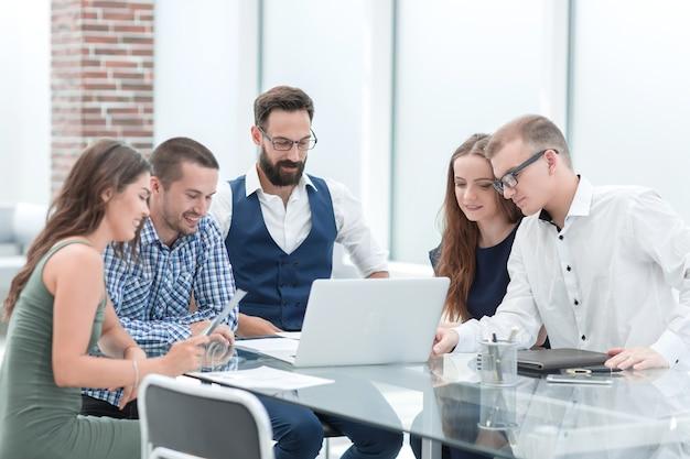 Uśmiechnięty zespół biznesowy patrzący na ekran laptopa. ludzie i technologia