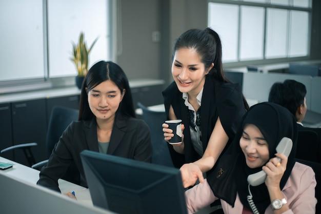 Uśmiechnięty zespół kobiet biznesu pracujący przy biurku i omawiający projekt na komputerze