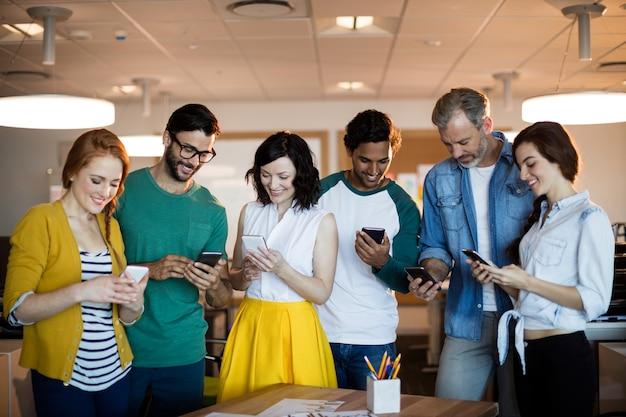 Uśmiechnięty zespół kreatywnych biznes za pomocą telefonu komórkowego w biurze