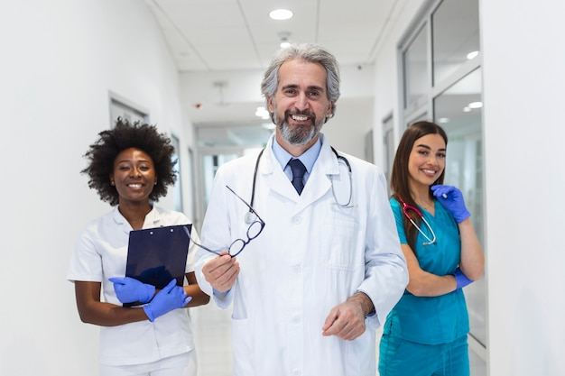 Uśmiechnięty zespół medyczny stojący razem w szpitalu, zawód