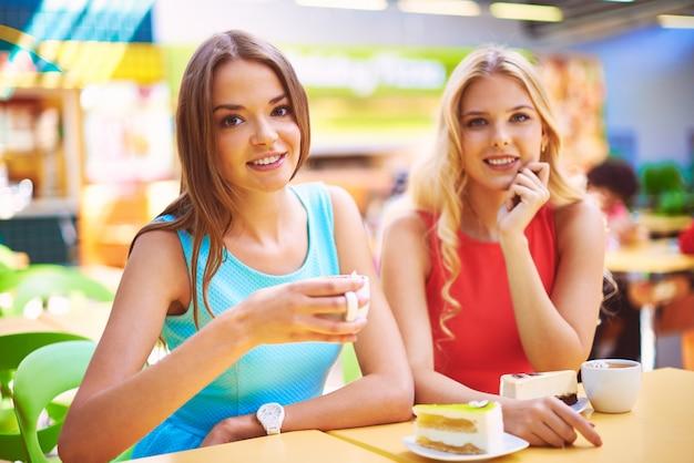 Uśmiechnięty znajomych korzystających filiżankę herbaty i kawałek ciasta