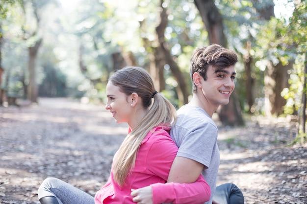 Uśmiechnięty znajomych rozciągające razem siedzi w parku