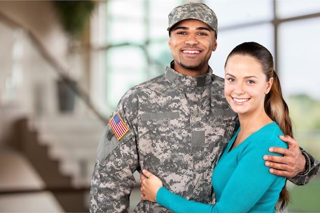 Uśmiechnięty żołnierz z żoną stojący na tle