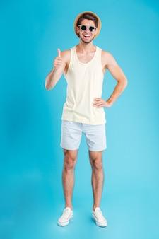 Uśmiechnięty zrelaksowany młody mężczyzna w kapeluszu i okularach przeciwsłonecznych stoi i pokazuje kciuki nad niebieską ścianą
