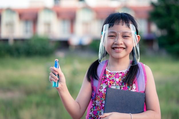 Uśmiechnij małą studentkę noszącą osłonę twarzy podczas jej powrotu do szkoły po kwarantannie covid-19.