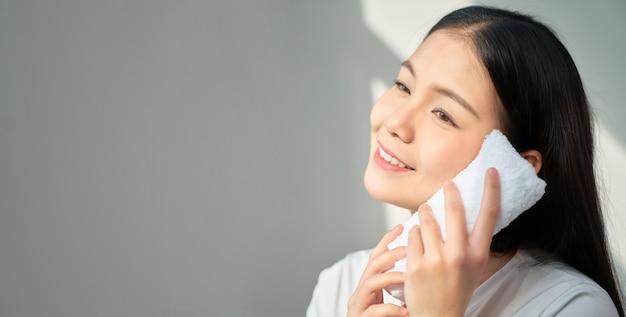 Uśmiechnij się azjatycka kobieta trzymając się za ręce biały ręcznik i dotykając twarzy.