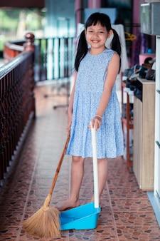 Uśmiechnij się azjatycka mała dziewczynka zamiatająca miotłą i szufelką w domu
