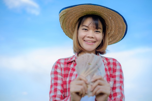 Uśmiechnij się azjatycki rolnik posiadający pieniądze banknotów na tle błękitnego nieba. obraz twarzy i niebieskie ręce ostrości.