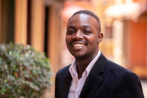 Uśmiechnij się biznesmen afryki stojący w mieście