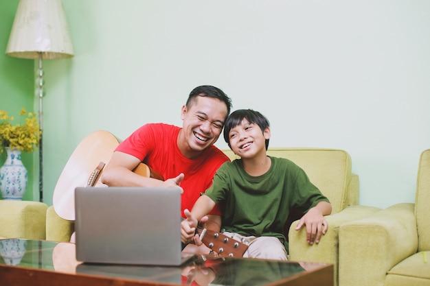 Uśmiechnij się tata i syn z kciukiem do góry gestem w kierunku laptopa podczas wideokonferencji