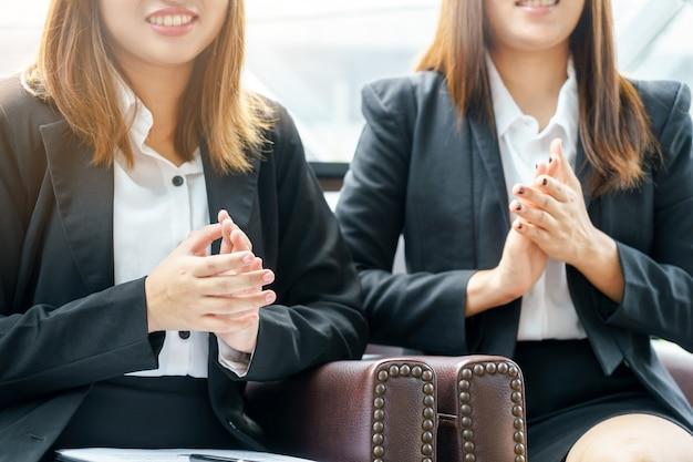 Uśmiechu bizneswoman klascze ręki podczas gdy siedzący pojęcie.