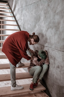 Uspokajająca dziewczyna. chłopak uspokaja swoją emocjonalną dziewczynę siedzącą na schodach i płaczącą po wielkiej kłótni