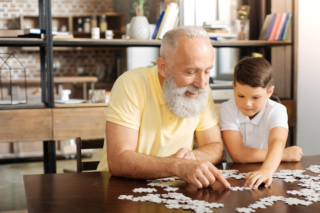 Uspokajająca rozrywka. szczęśliwy starszy mężczyzna siedzi przy stole obok swojego małego wnuka i próbuje zrobić z nim dużą układankę