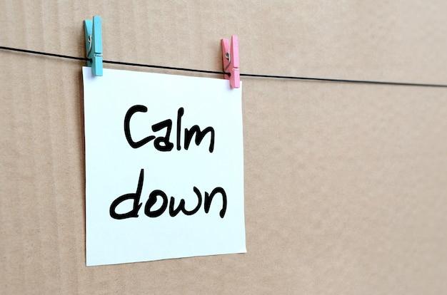 Uspokój się. uwaga jest zapisana na białej naklejce, która wisi na spinaczu na linie na tle brązowej tektury
