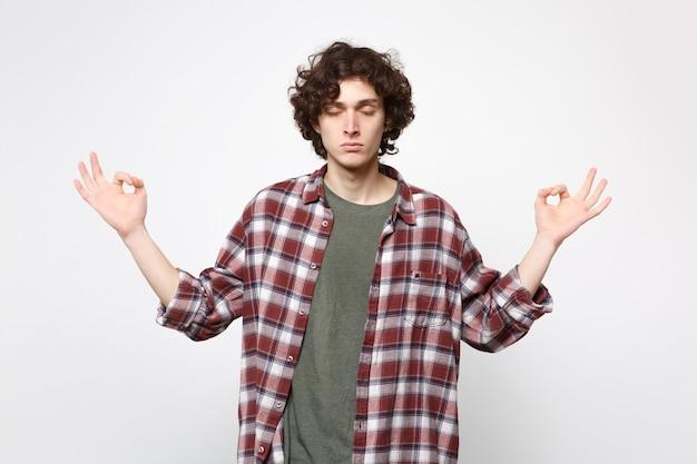 Uspokojony młody człowiek w ubranie trzymając zamknięte oczy trzymać ręce w geście jogi relaksujący medytacji na białym tle na tle białej ściany. ludzie szczere emocje, koncepcja stylu życia. makieta miejsca na kopię.