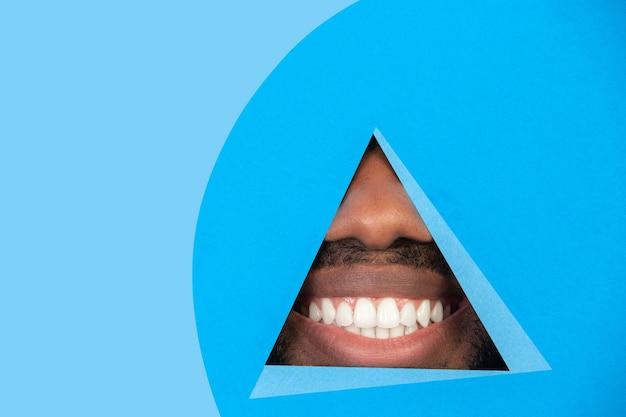 Usta afroamerykańskiego mężczyzny zerkające przez trójkąt na niebieskim tle