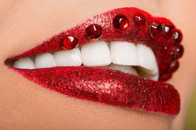 Usta pomalowane czerwoną szminką i koralikami