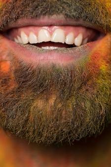 Usta toothy uśmiechnięty brodaty mężczyzna z tęczy farbą na twarzy