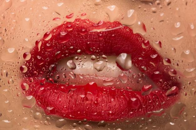 Usta z bliska czerwona szminka. krople wody na szybie.