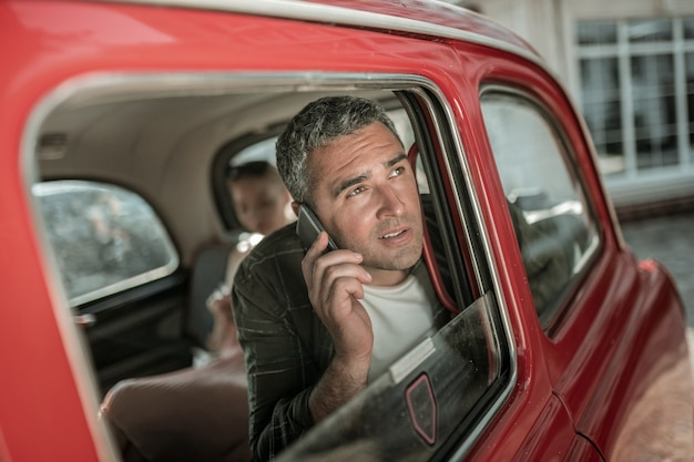 Ustalenie spotkania. uśmiechnięty mężczyzna rozmawia przez telefon, siedząc w pobliżu okna samochodu przed żoną.