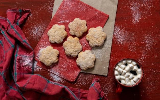 Ustaw ciastka na czerwonym drewnianym stole z czerwoną filiżanką kawy i torbą na zakupy, koncepcja dostawy.