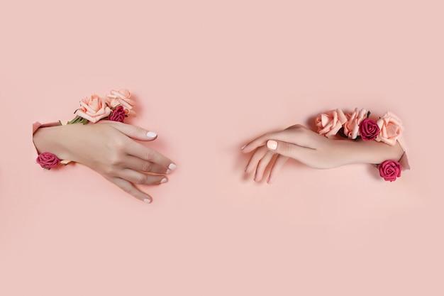 Ustaw dłonie ze sztucznymi kwiatami wystającymi z różowej papierowej ściany. podaj w różnych pozach, układ wzoru dla swojego kolażu. kosmetyki do pielęgnacji skóry dłoni, nawilżania i redukcji zmarszczek