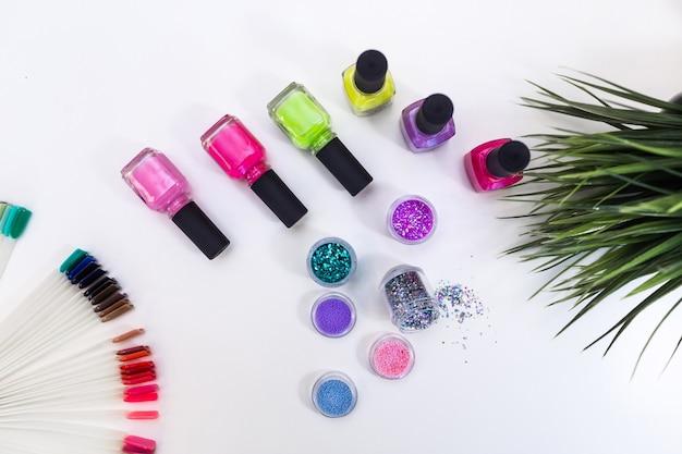 Ustaw manicure w wielu kolorowych lakierach do paznokci i mieni się połyskiem na białym stole z bliska.