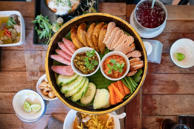 Ustaw przystawkę kuchni północno-tajskiej ze smażoną wieprzowiną, kiełbasą, warzywami i sosem tajskim chili na khantoke lub tradycyjnym pojemniku w restauracji
