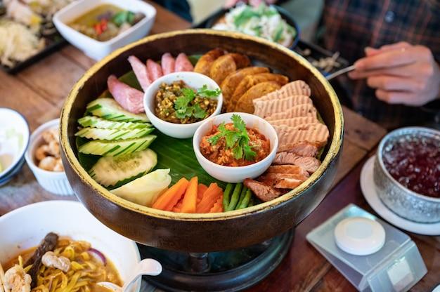 Ustaw przystawkę z północnotajlandzkiego jedzenia ze smażoną wieprzowiną, kiełbasą, warzywami i dipem z tajskiego sosu chili na khantoke lub tradycyjnym pojemniku