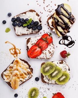 Ustaw słodkie kanapki ze świeżymi jagodami i owocami