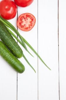 Ustaw świeże warzywa na biały drewniany stół. pomidor, ogórek i zielona cebula. widok z góry
