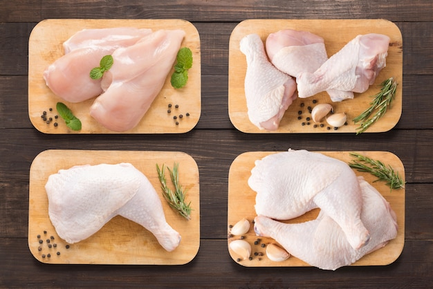 Ustawia surowego kurczaka na tnącej desce na drewnianym tle