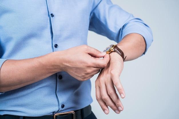 Ustawiam zegar. człowiek wiatr zegarek na rękę szarym tle. przenośny zegarek. zarządzanie czasem. ostateczny termin. zegar tyka.
