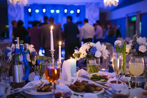 Ustawienia stołu weselnego w restauracji. ludzie tańczący w tle stołu dla nowożeńców.