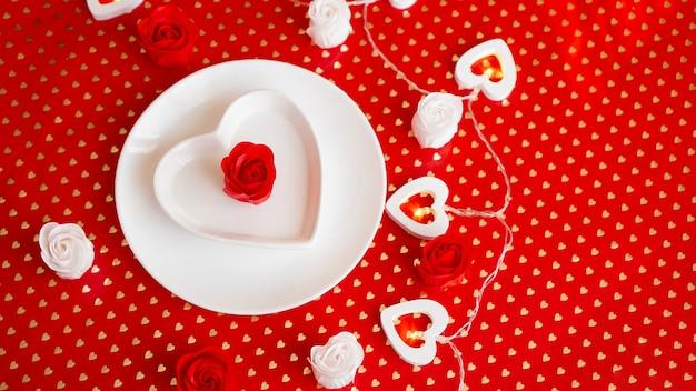 Ustawienie miejsca w kolorze czerwonym i białym - na walentynki lub inne wydarzenie. biały talerz w kształcie serca z dekoracją róż na czerwonym tle